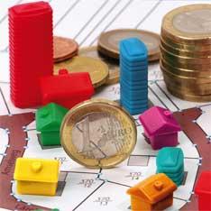 Bild mit Monopoly Häusern, Geld und Katasterkarte. Darstellung des Grundstückwertes